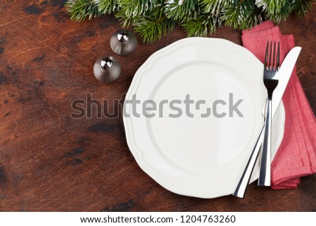 Christmas table setting with empty plate, silverware and fir tree branch covered by snow on wooden background. Top view with space for your greetings