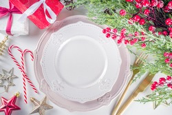 Christmas table setting with empty plates, gift box and xmas decor. Top view flat lay with copy space, white background
