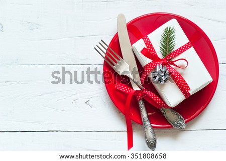 Christmas table setting with gift at white table. Top view, copyspace.