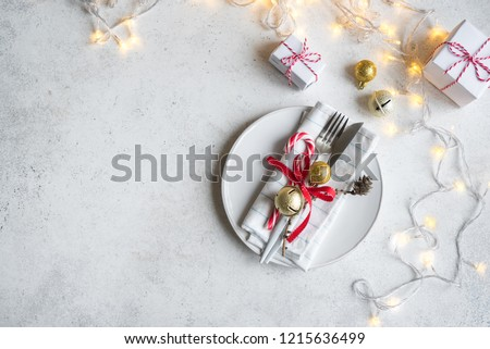 Christmas Table Setting with  lights and gift boxes on white table, copy space. Christmas dinner, party design, concept.