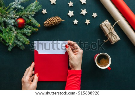 Christmas table with various items. Woman\'s hands putting a letter in an envelope