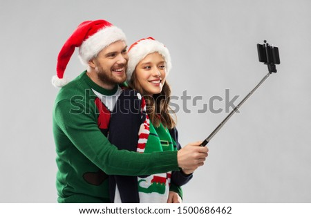 christmas, technology and holidays concept - happy couple in santa hats taking picture by smartphone on selfie stick at ugly sweater party