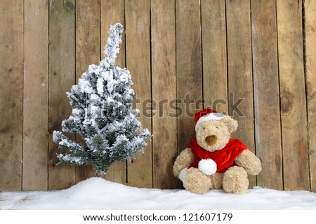 christmas teddy bear sitting in the snow, wooden background