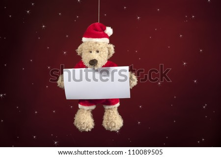 Christmas teddy bear with wishes card on red star background