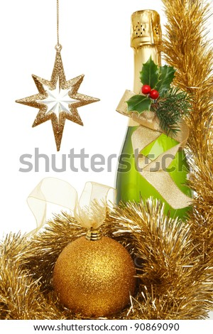 Christmas theme,bottle of champagne decorated with holly, pine needles and a gold ribbon bow surrounded by tinsel and gold glitter bauble and gold star
