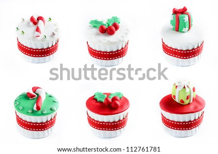 Christmas theme cupcakes in traditional red green colours and elements presents gifts candy cane mistletoe from overhead