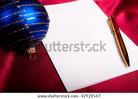 Christmas theme. Pen, paper and blue ball.