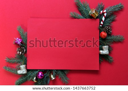 Christmas theme. Red background with green branches of spruce and various Christmas toys. Background, postcard, free space in the center, horizontal. Christmas and New Year concept.