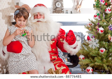 Christmas theme: Santa Claus and little girl having a fun. Indoors at home near christmas tree.