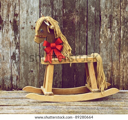Christmas themed image with an antique rocking horse with a sparkling red Christmas bow around his neck on a rustic wooden backdrop.