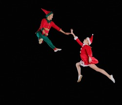 Christmas time, childhood, fairy tale. A young girl wearing a Santa's costume and boy wearing elf costume flying together