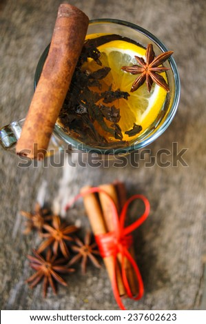 Christmas time, cup of tea with cinnamon and anise spices, festive decoration and candles