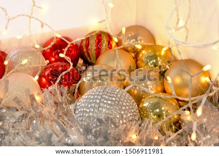 Christmas time decorating. Time to decorate interior with beautiful Christmas balls garland lights, tinsel and other Christmas decor. Decorations in the box lighted with garland light bulbs. Shiny pic