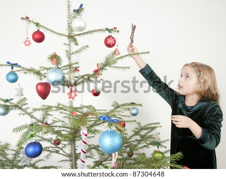 Christmas time - little girl decorating a Christmas tree - stock photo