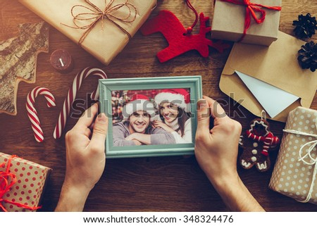 Christmas together. Top view of Christmas decorations and photograph in picture frame laying on the rustic wooden grain