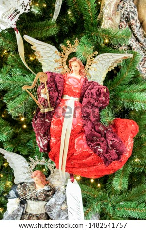Christmas toy angel on spruce branches. Christmas tree decorations and decorations in the design.