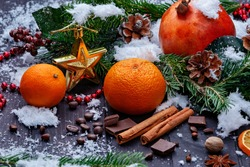 Christmas toy, anis stars, dried oranges, tangerines, cinnamon sticks, berries, nuts and cones on black wooden background. Christmas or winter composition. Christmas time. Winter holidays concept.
