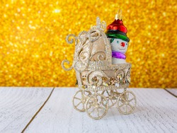 Christmas toy baby carriage on a gold background. Snowman peeking out of a baby carriage. Blurred background.