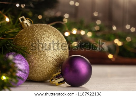Christmas toy golden ball next to a purple ball with a pattern on a light table in the background a Christmas tree with a garland next to a wooden wall