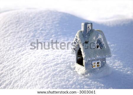 Christmas toy house on the snowdrift and sun shadows