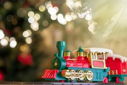 Christmas toy train on Christmas tree background with defocused lights. Copy space for text. Selective focus.