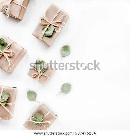 christmas toys and craft boxes on white background. creative arrangement frame of craft boxes and green branches eucalyptus on white background. flat lay, top view