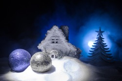 Christmas toys at decorative fir-tree in snow. Making a Christmas tree on table. Empty space. Useful as greeting card