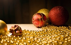 Christmas toys gold and red with gold beads on the table. Red ball with gold pattern. New year's footage with the Christmas tree decorations in warm colors