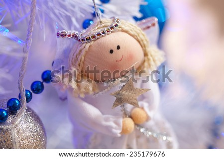 Christmas toys in the form of an angel hanging on the tree next to the balls and beads