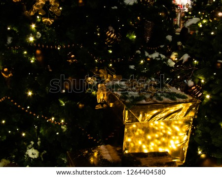 Christmas toys on fir tree closeup photo. Merry Christmas and Happy New Year postcard. Sparkling X-mas decor. Golden gift box under conifer tree. Natural Christmas firtree. Lush spruce branches. #1264404580