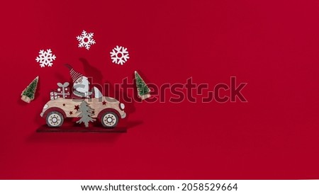 christmas toys santa claus by car christmas trees and snowflakes on a red background composition
