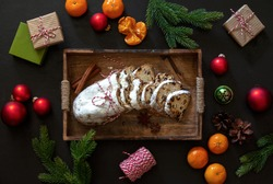 Christmas traditional fruit bread stollen lying down in a wooden tray on dark kitchen table, top down view on holliday treats, gift boxes and home Xmas decorations