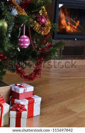 Christmas tree and christmas gift boxes in  interior with  fireplace