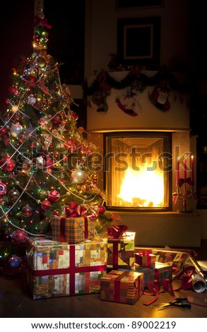 Stock Photo Christmas Tree and Christmas gift boxes in the interior with a fireplace