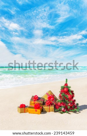 Christmas tree and gift boxes with big red bows on sandy beach. New Year\'s vacation concept.