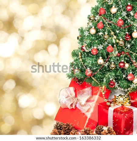 Christmas tree and gifts over golden sparkle background.