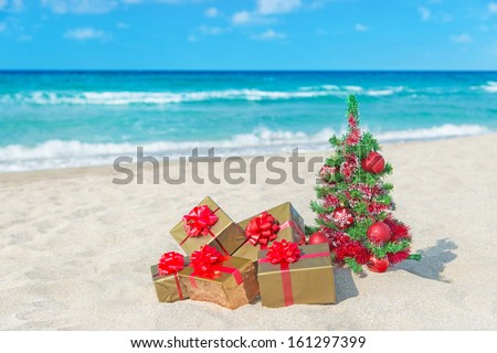 Christmas tree and golden gift with big red bow on the sea sandy beach Christmas vacation concept