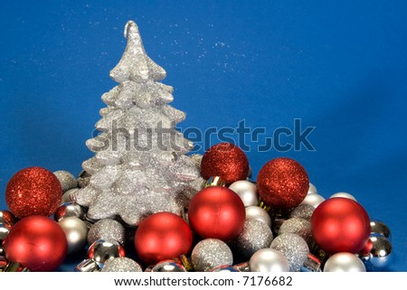 Christmas tree and small silver and red globes on blue