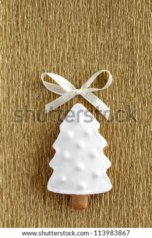 Christmas tree background. Ginger and Honey cookie in the shape of a fir tree with white sugar decoration and bow on the gold wrapping paper background