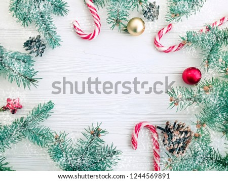 Christmas tree branch, pinecone, candy on a white wooden background frame, snow #1244569891