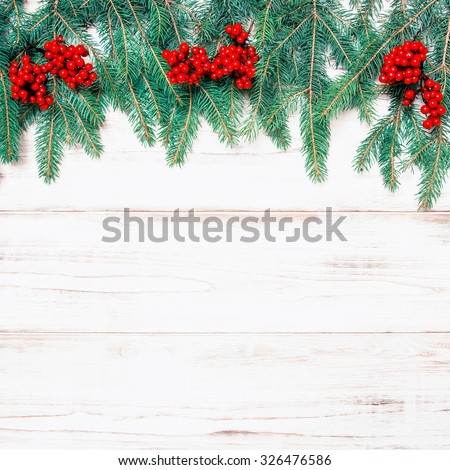Christmas tree branch with red berries on wooden background. Winter holidays decoration. Retro style toned picture #326476586
