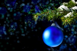Christmas tree branch with snow and blue ornament. New year greeting background. Copy space.