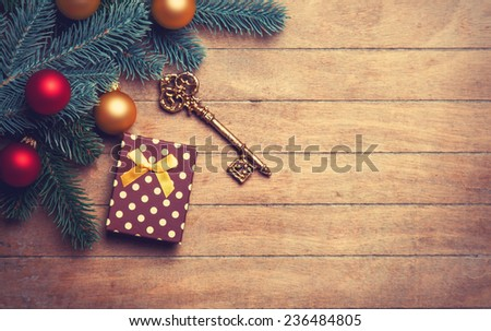 Christmas tree branch with toy balls and gift on wooden table.