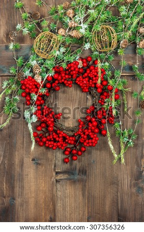 Christmas tree branches and wreath from red berries over rustic wooden