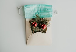 Christmas tree branches in envelope with mask. Minimal, creative Covid-19 New Year's card. Pine tree branch with pearls on white background. Holidays, Congratulation, Christmas, Coronavirus concept.