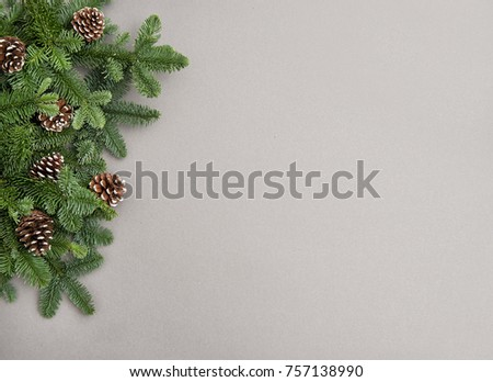 Christmas tree branches with cones on gray background. Minimal winter backdrop #757138990