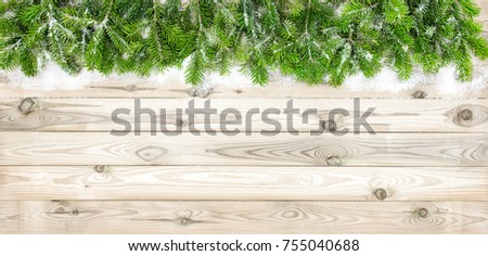 Christmas tree branches with snow decoration on wooden texture. Winter holidays background #755040688