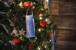 Christmas tree 2021 composition decorated with blue medical corona virus face masks and winter ornaments with sparkling lights on blurred wood background. Merry Christmas in covid-19 pandemic.