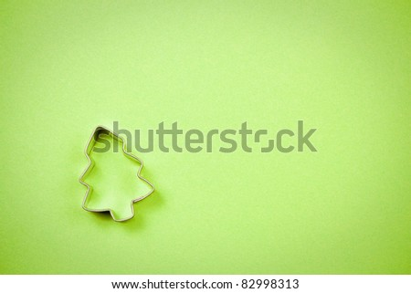 Christmas tree cookie cutter on a sheet of textured green paper, room for copy.