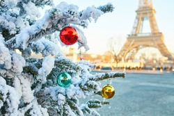 Christmas tree covered with snow and decorated with red, green and yellow balls, Eiffel tower in the background. Season holidays in Paris, France
